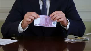 Businessman s hands tear money and throw it