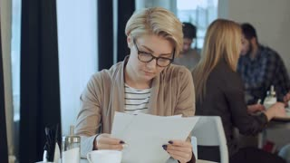 Businesswoman working with documents in coffee shop