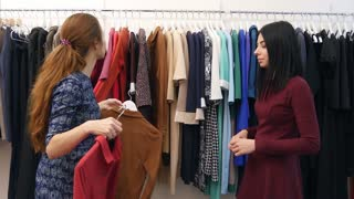 Cheerful saleswoman serving client, help to wear dress near wardrobe in boutique