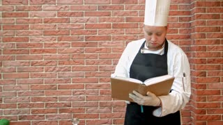 Chef cook holding recipes book thinking what to cook