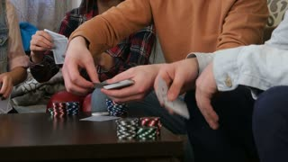 Company of friends sitting at table at student house and playing poker game