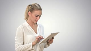 Concentrated businesswoman standing with digital tablet on white background
