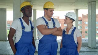 Confident diverse team of workmen and women standing grouped in their dungarees and hardhats smiling at the camera