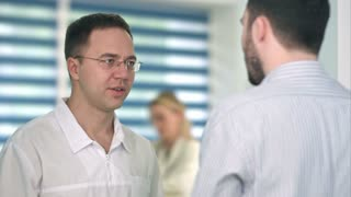 Confident male doctor talking to male patient