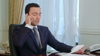Confident young businessman takes a call in a modern office