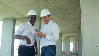 Construction builders smiling while using smartphone at site