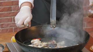 Cooking seafood in large flame