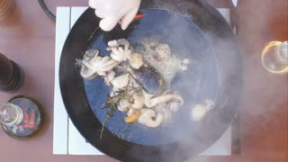 Cooking seafood in pan with flame