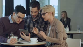 Creative team using smartphone and talking in casual office