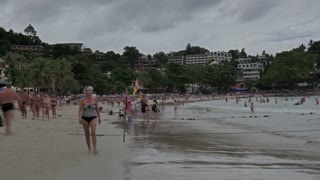 Crowd of people have a rest at cloudy day on the beach at Phuket, Thailand