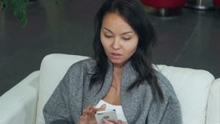 Cute asian woman relaxing on sofa and using smartphone