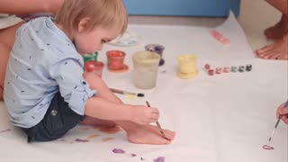 Cute little baby boy painting his feet on a large blank white paper