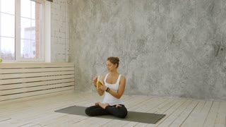 Cute young woman chewing a banana while sitting on exercise mat