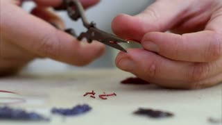 Cutting red wire into small peaces with scissors