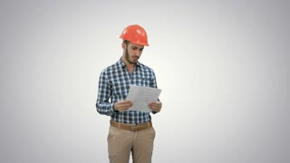 Engineer in hardhat looking at construction plan on white background