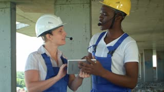 Engineers on building site using digital tablet and talking
