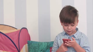 Excited little boy reading a message on his phone