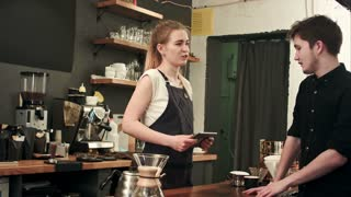 Female barista talking to customer in a cafe, taking order