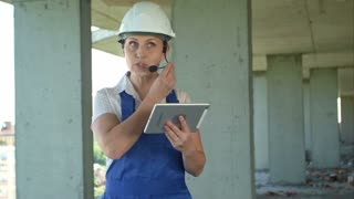 Female construction engineer reading plans using digital tablet and talk to workers through internal links