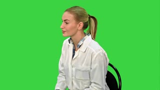Female doctor talking with patient and writing a recipe on a Green Screen, Chroma Key