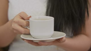 Female hand holding cup of black coffee