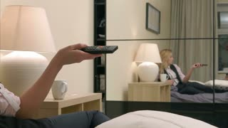 Female hand switch TV channels in bed
