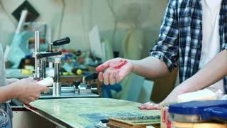 Female hands carefully bandaging worker injured hand after accident