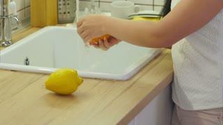 Female hands washing orange in the water