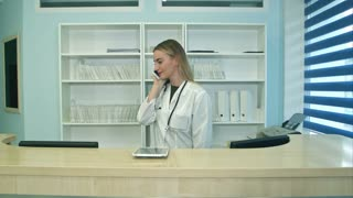 Female nurse at hospital reception answering phone calls and scheduling patient appointments
