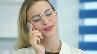 Female nurse at hospital reception talking on the phone