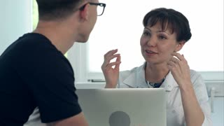 Friendly female doctor consulting male patient sitting at desk with laptop