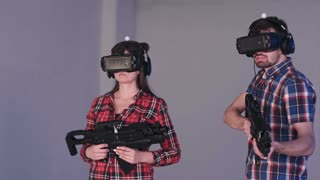 Friends playing VR shooter game with virtual reality guns and glasses