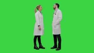 Funny male doctor kidding on female nurse give a false hi five on a Green Screen, Chroma Key