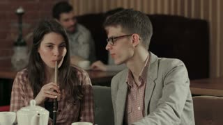 Girl and guy smoke hookah