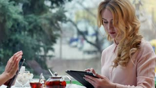 Girls use their break from work to drink coffee, chat and use digital tablet