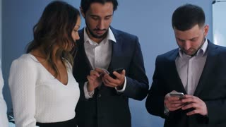 Group of five multiracial business people standing and using smartphones