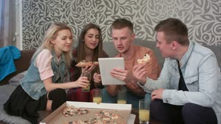 Group of friends eating takeaway pizza and watching programm on tablet