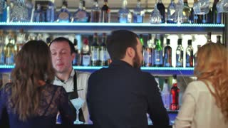 Group of friends relaxing on party in bar, talking with bartender