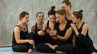 Group of girls in fitness class at the break looking at cell phone, happy and smiling, show funny face