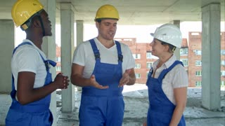 Group of smiling builders in hardhats talking at construction site