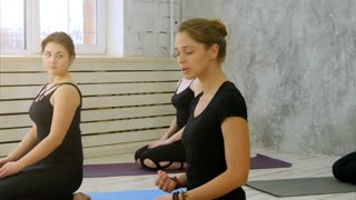 Group of smiling women listen to a yoga instructor in fitness studio