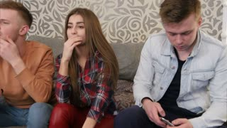 Group of young friends watching television together on couch, communicating, using cell phones