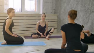 Group smiling women before training talking and stretching in yoga class