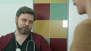 Gynecologist doctor talking with pregnant woman at hospital