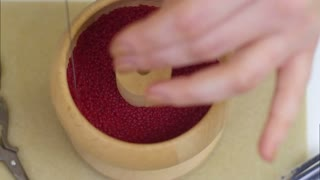 Hands carefully setting red beads for a new jewellery