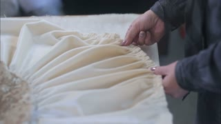Hands of designer at work with fabric