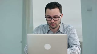 Handsome male teacher in glasses typing on laptop