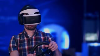 Happy and excited man playing racing video game with virtual reality headset