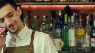 Happy barman in apron calling on smartphone at bar