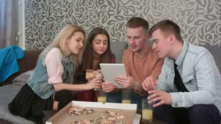 Happy diverse group of friends laughing at what they see on the screen of a computer tablet